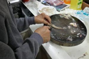図6. メゴチさばき:背びれを後ろから切り、頭の付け根で入刃して骨を断つ。